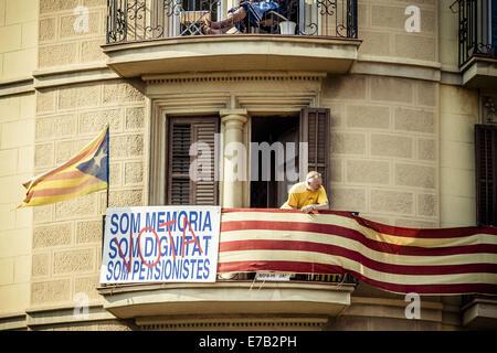 Barcelona, Spanien. 11. September, 2014. Ein Rentner auf seinem Balkon mit Blick auf Tausende von Katalanen in roten - Stockfoto