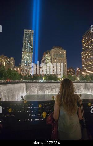 New York, NY, USA. 11. September, 2014. Der Tribute in Light ist hinter den 9/11 Memorial Wasserfällen und Wasserbecken - Stockfoto