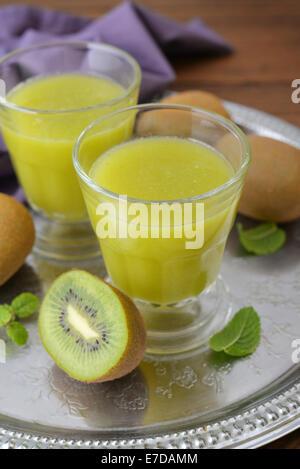 Kiwi-Saft mit frischer Kiwi und Minze im Glas auf hölzernen Hintergrund - Stockfoto