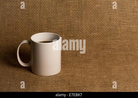 Kaffee-Haferl hautnah.  Weiße Tasse auf Sackleinen.  Kopieren Sie Raum.  Warme Töne. - Stockfoto