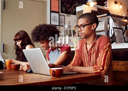 Personen mit Technologie im Coffee-shop