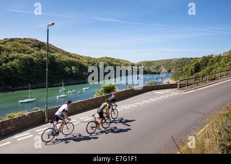 Drei Radfahrer Fahrt entlang einer Straße am Hafen von Pembrokeshire, Wales - Stockfoto