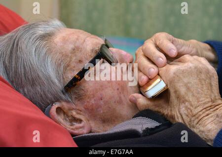 Alter Mann spielen Mundharmonika im Bett. Konzept, Foto von old Age, einsam, allein, Pensionierung, Musik, traurig. - Stockfoto