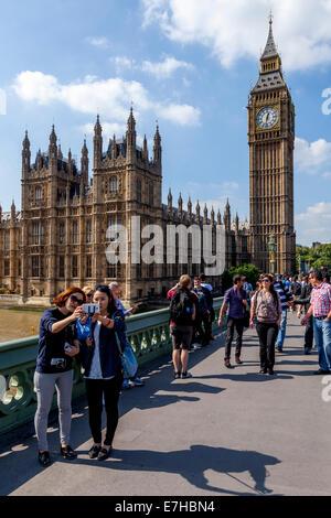 Touristen posieren vor den Houses Of Parliament und Big Ben, London, England - Stockfoto