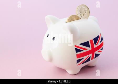 Sparschwein mit britischen Union Jack und zwei Pfund Sterling Pfund-Münzen in den Schlitz auf einem rosa Hintergrund. - Stockfoto
