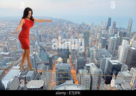 Geschäftsfrau, die zu Fuß auf Drahtseil mit Stadt im Hintergrund - Stockfoto