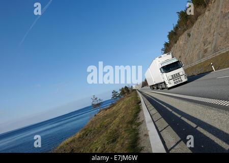 große LKW-fahren auf malerische Autobahn, Meer im Hintergrund - Stockfoto