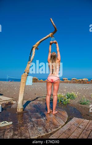 Ein blondes Mädchen trägt ein rosa Bikini Duschen unter einer provisorischen Dusche an einem Strand in der heißen - Stockfoto