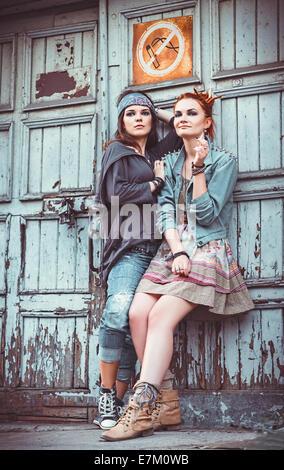 Zwei schöne Grunge Mädchen an einer Wand stehend - Stockfoto