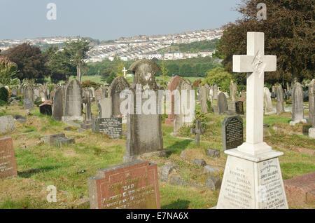 Reihen von Reihenhäusern mit Schieferdächern Kontrast zu den Gang und die Reihe der Grabstein im Friedhof erinnert - Stockfoto