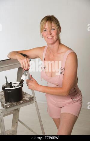Malerin Dekorateur tragen Lätzchen und Hosenträger Overalls mit Pinsel und Leiter - Stockfoto