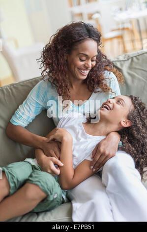 Mutter Tochter (8-9) auf Sofa kitzeln - Stockfoto