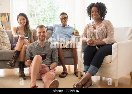 Porträt der Gruppe von Freunden im Wohnzimmer sitzen - Stockfoto