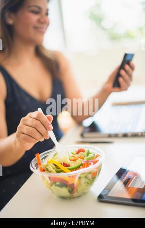 Frau Salat essen und mit Handy im Büro - Stockfoto