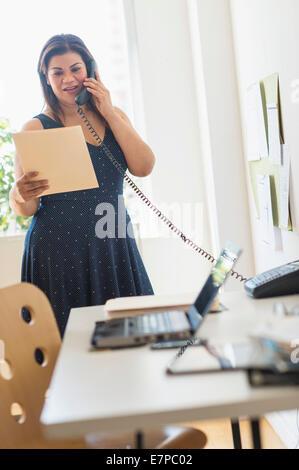 Frau mit Telefon im Büro - Stockfoto