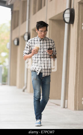 Mann zu Fuß auf dem Bürgersteig mit Eiskaffee und Handy - Stockfoto