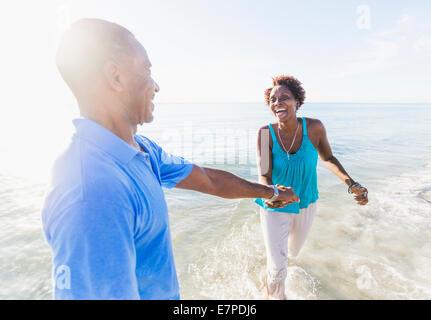 Älteres Paar zu Fuß am Strand - Stockfoto