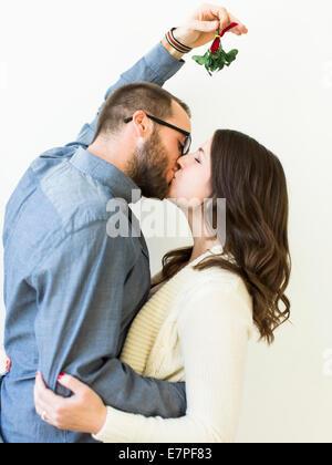 Paar unter Mistelzweig küssen - Stockfoto