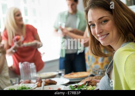 Ein Familientreffen für eine Mahlzeit. Erwachsene und Kinder an einem Tisch. - Stockfoto