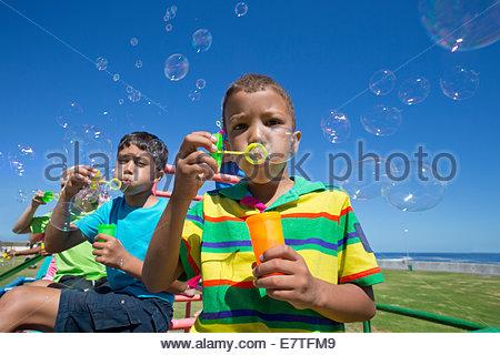 Kinder Seifenblasen mit Blase Zauberstäbe auf Spielplatz - Stockfoto