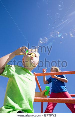Kinder Seifenblasen auf Klettergerüst auf Spielplatz - Stockfoto