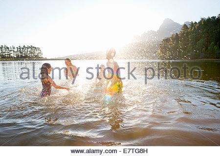 Familie, die einander im See plantschen - Stockfoto