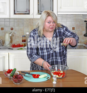 Dicke Frau in der Küche macht Salat - Stockfoto