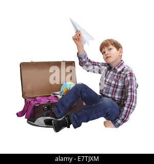 Junge sitzt in der Nähe von offenen Koffer in der hand mit Papierflieger isoliert auf weißem Hintergrund - Stockfoto