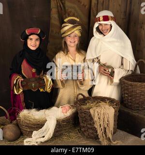 Drei Mädchen spielen als weisen mit einer Puppe in eine Weihnachtskrippe - Stockfoto