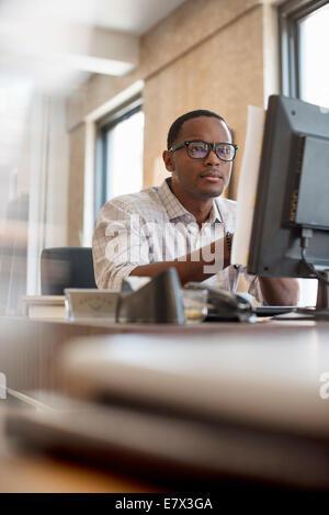 Büroalltag. Ein Mann sitzt an einem Schreibtisch mit einem Computer. - Stockfoto