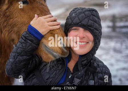 Frau mit Islandpferd in einem Schneesturm, Island - Stockfoto