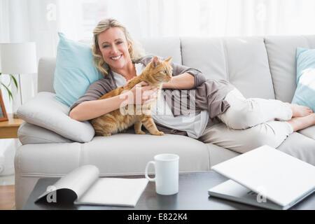 Fröhliche Frau, die auf Sofa kuscheln eine Ingwertee Katze - Stockfoto