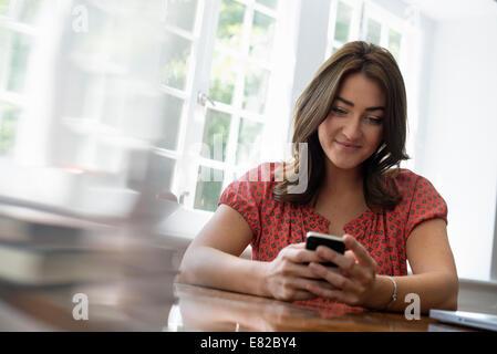 Eine Frau an einem Tisch sitzen ihr Smartphone überprüfen. - Stockfoto