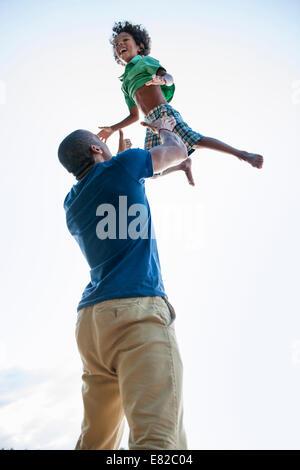 Ein Mann, einen kleinen Junge hob über seinem Kopf im Spiel. - Stockfoto