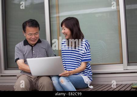 Ein Mann und eine Frau sitzen vor einem Haus. Halten einen Laptop-Computer. - Stockfoto