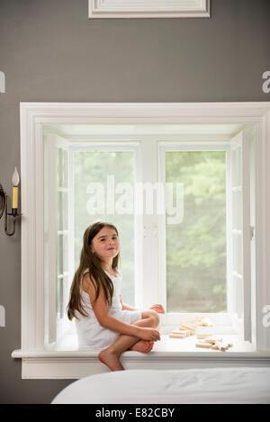 Ein Mädchen in einem weißen Kleid, durch das eine Fenster spielen sitzen. - Stockfoto