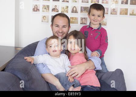 Vater und Kinder sitzen zusammen auf Sofa, Porträt - Stockfoto
