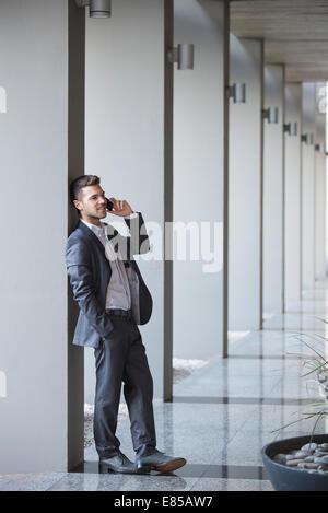Junge executive unter Anruf während gelehnt Spalte beim Aufbau lobby - Stockfoto