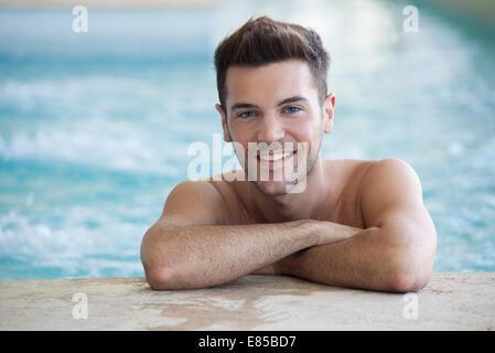 Junger Mann im Pool an Wand - Stockfoto