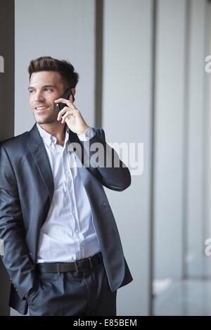 Junger Mann gelehnt Buiding Spalte reden über Handy - Stockfoto