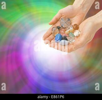 Heiler mit hohlen offenen Handflächen hält eine Auswahl an Heilung Kristalle auf einem spiralförmigen grün und lila - Stockfoto