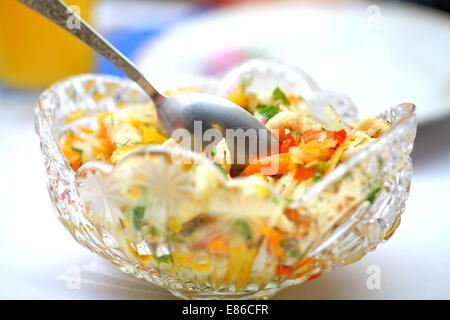 Gesunder Salat mit Garnelen auf dem Teller und Löffel