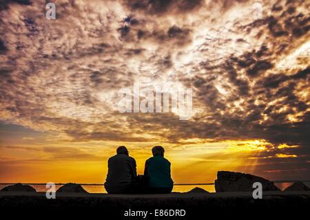 Älteres Paar mit Blick auf den Sonnenuntergang über Adria in Duino, Italien - Stockfoto