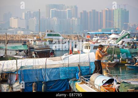 Chinesischer Mann auf einem Boot in der schwimmenden Dorf. Causeway Bay Typhoon Shelter, Hong Kong. - Stockfoto