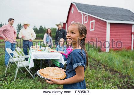 Lächelndes Mädchen mit Torte außerhalb Scheune - Stockfoto