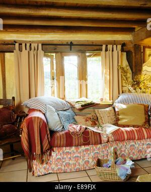 Sofa Mit Kissen Stapelten Und Wirft Vor Fenster Cremefarbenen Vorhngen Im Wohnzimmer Holzbalken Land