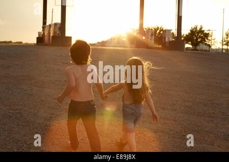Geschwister, die Hand in Hand an Tankstelle - Stockfoto