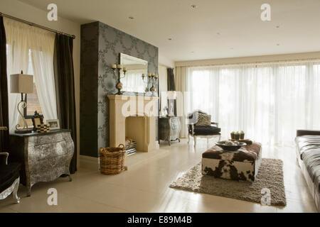 Bow fronted Kabinett am Kamin im Wohnzimmer mit Kuh Fell bedeckt osmanischen - Stockfoto