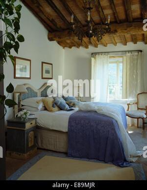 Blauer Baumwollbezug auf Polsterbett in toskanischen Schlafzimmer mit bemalten Nachttisch Schrank und rustikale - Stockfoto