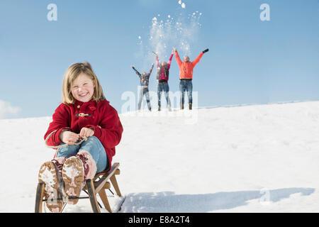 Porträt von Mädchen sitzen auf Schlitten, Familie, spielen im Hintergrund, Bayern, Deutschland - Stockfoto